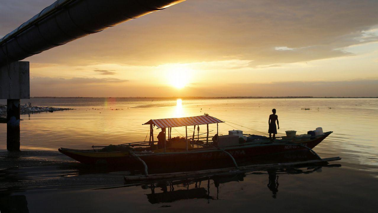 Un pescador maniobra en su barco durante el atardecer en la Bahía de Manila (Filipinas)