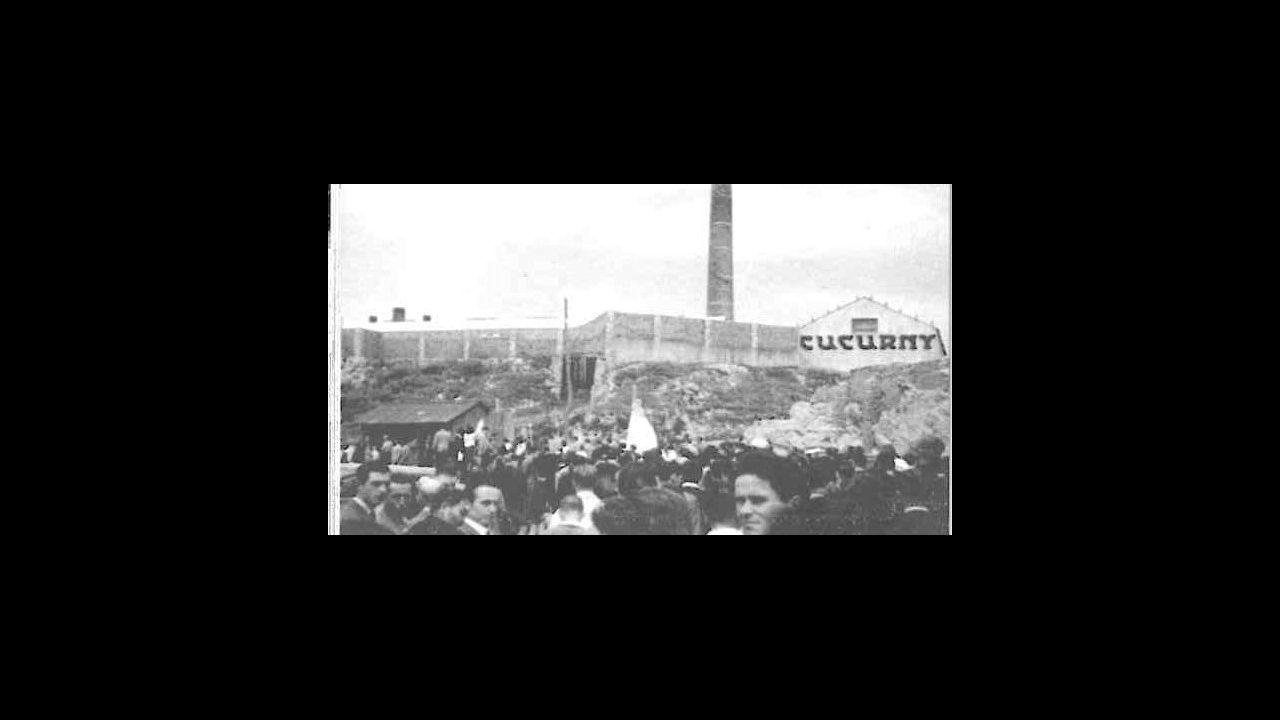 Procesión en Burela, con la chimenea de la fábrica al fondo