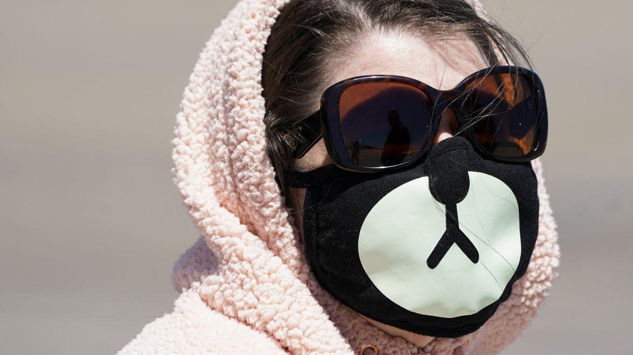 Una mujer luce una máscara facial dibujada en Maryland, donde han comenzado las restricciones