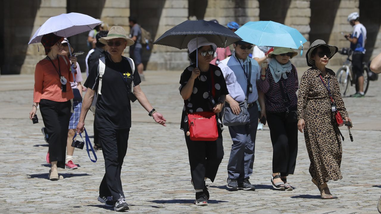 Turistas en la plaza de Obradoiro protegiéndose del sol