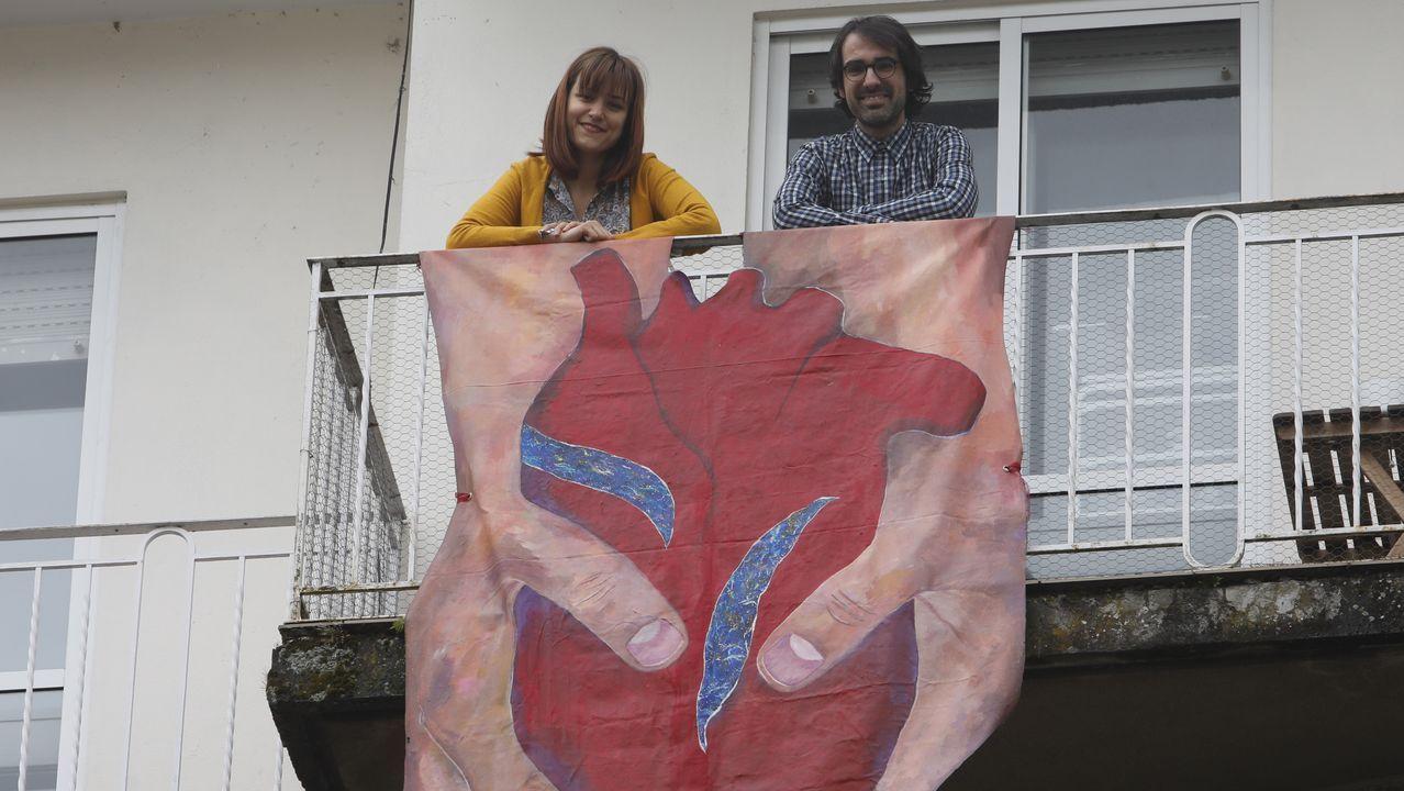La artista Iris Branco junto a su pareja, el diseñador Cristian Andrade, posando sonrientes junto a la obra que la ourensana ha colgado de su balcón