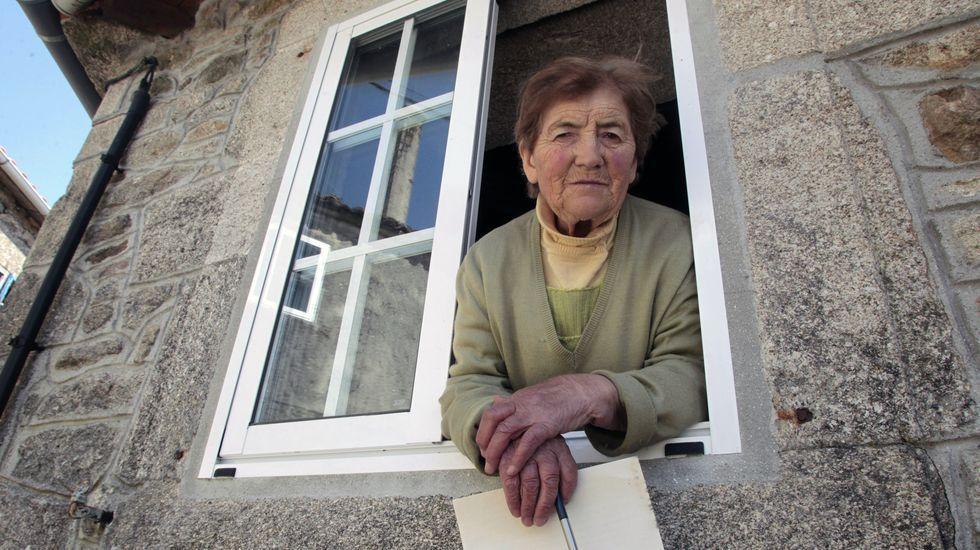 Visita Lamas, en una ventana de su casa este jueves, doce días después de que unos ladrones la asaltasen durante la noche
