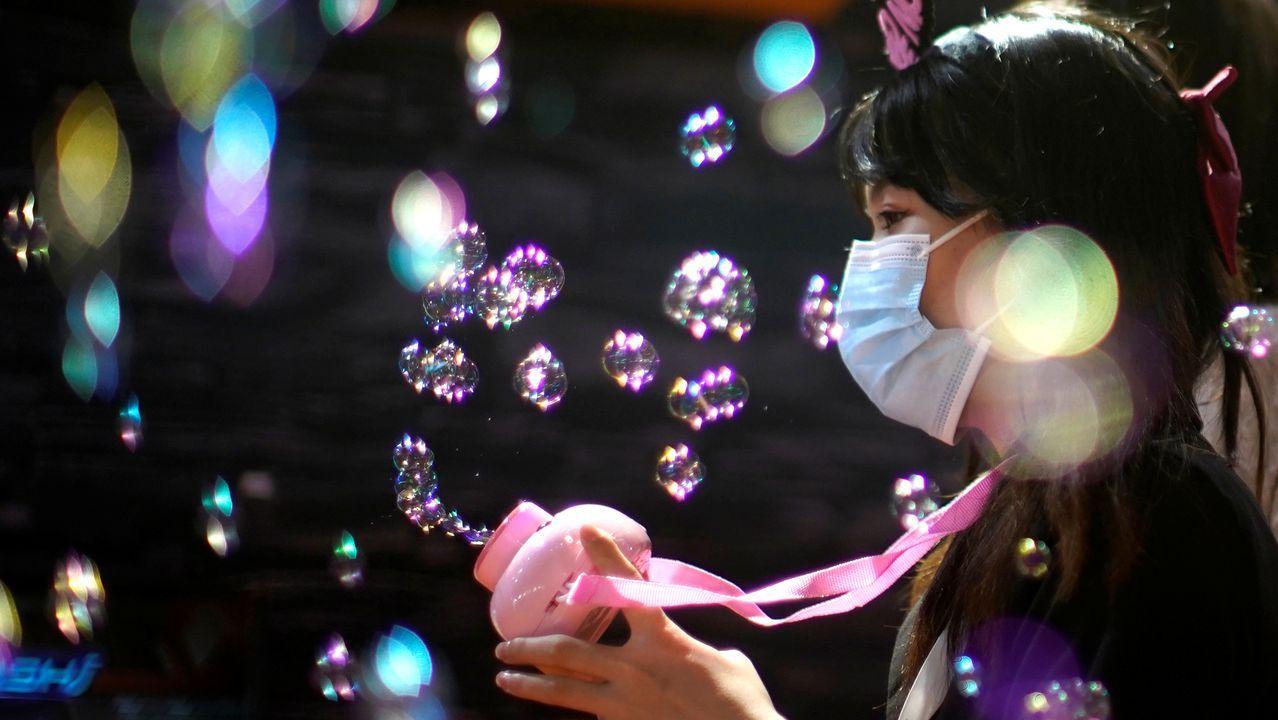Una niña con una máscara facial protectora juega con burbujas en la Exposición y Conferencia de Entretenimiento Digital de China (ChinaJoy) en Shanghai