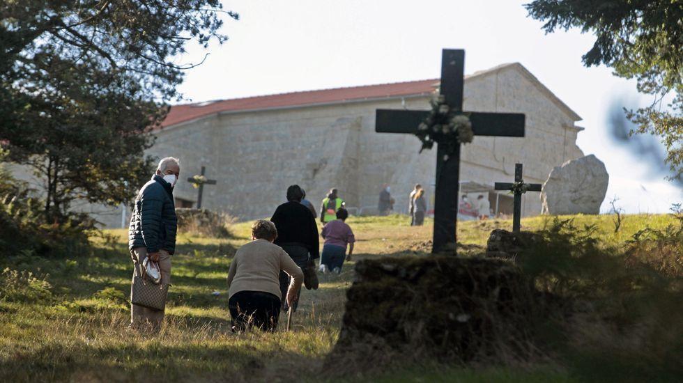 Fieles de rodillas en el tramo final de la subida, con la ermita de O Faro ya a la vista