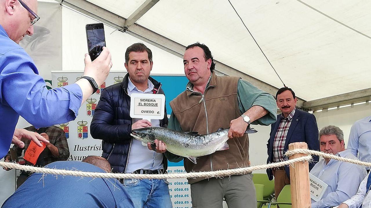 El pescador del campanu Fernando López Castro entre el campanu, pescado en el Cares, al representante del restaurante El Bosque, de Oviedo