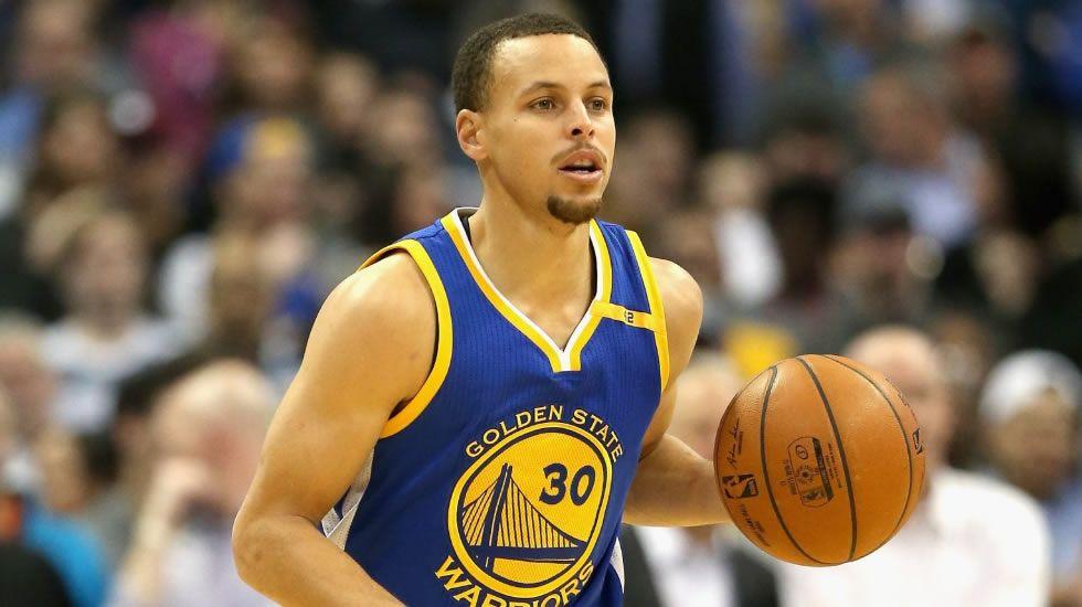 Curry conduce un balón durante un partido.