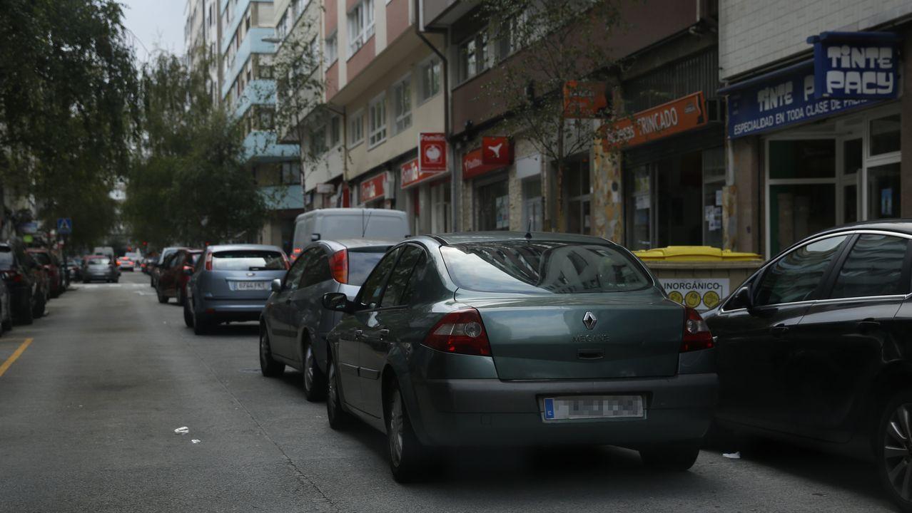 Hilera de coches aparcados en doble fila en una calle del Agra del Orzán