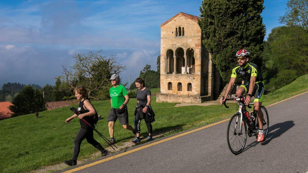 Personas descienden del monte Naranco ante la Iglesia de Santa María del Naranco, en un dia con menos paseantes en el segundo día que se permiten los paseos de adultos y el deporte individual al aire libre. EFE/Alberto Morante