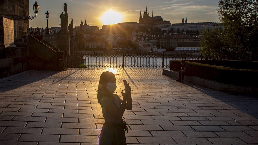 Una turista, que lleva mascarilla, mira el atardecer en Praga, República Checa