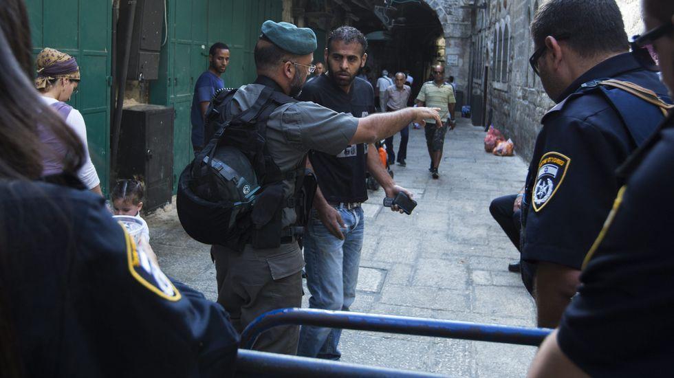 Un policía fronterizo israelí ordena a un palestino que se aleje de la calle cortada en el barrio musulmán de Jerusalén.