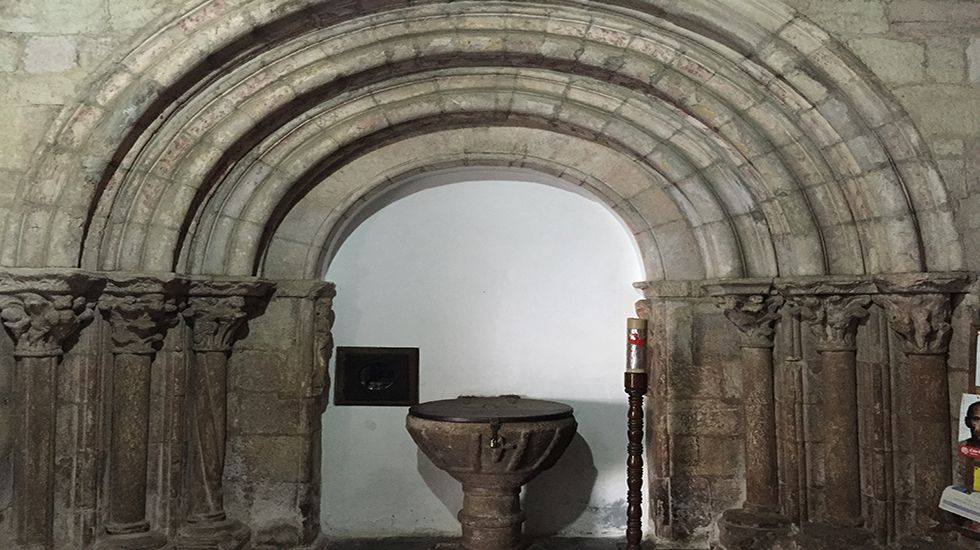 Portada románica y pila bautismal de la iglesia de San Salvador (Grandas de Salime).