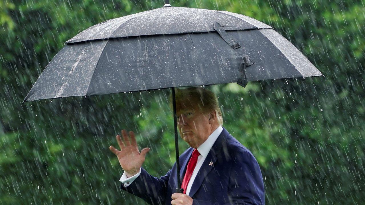 Donald Trump se protege de la lluvia, este jueves, al salir de la Casa Blanca para viajar a Dallas