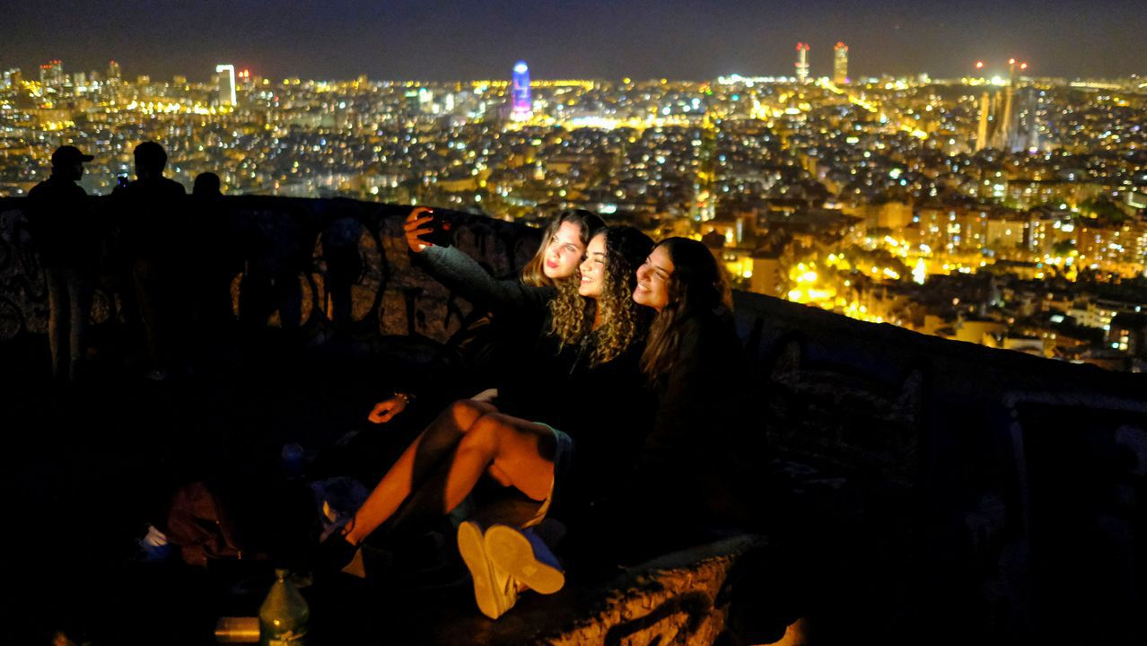 vacunas asturias .Tres jóvenes se sacan un selfie con Barcelona de fondo