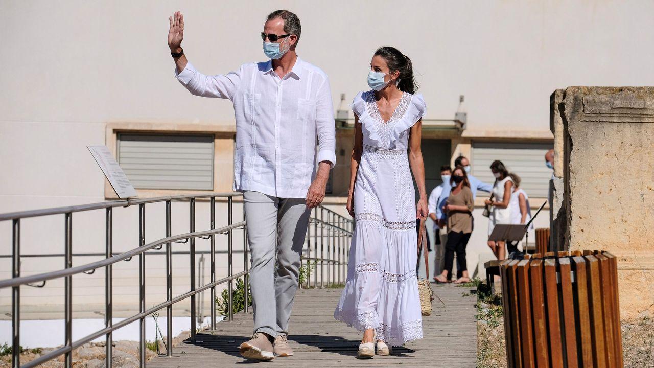El rey Felipe VI (i) y la reina Letizia saludan durante su visita a Ibiza, este lunes. Los reyes han visitado la necrópolis fenicio-púnica de Puig des Molins así como el museo monográfico junto al yacimiento, el primer acto que han protagonizado después de que se desvelara que don Juan Carlos está en Emiratos Árabes Unidos