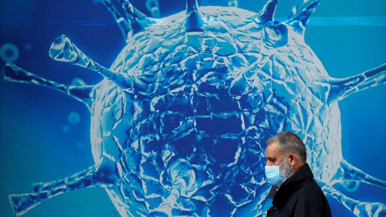 Un hombre con mascarilla pasa junto al centro de investigación del covid-19 en Oldham, Reino Unido