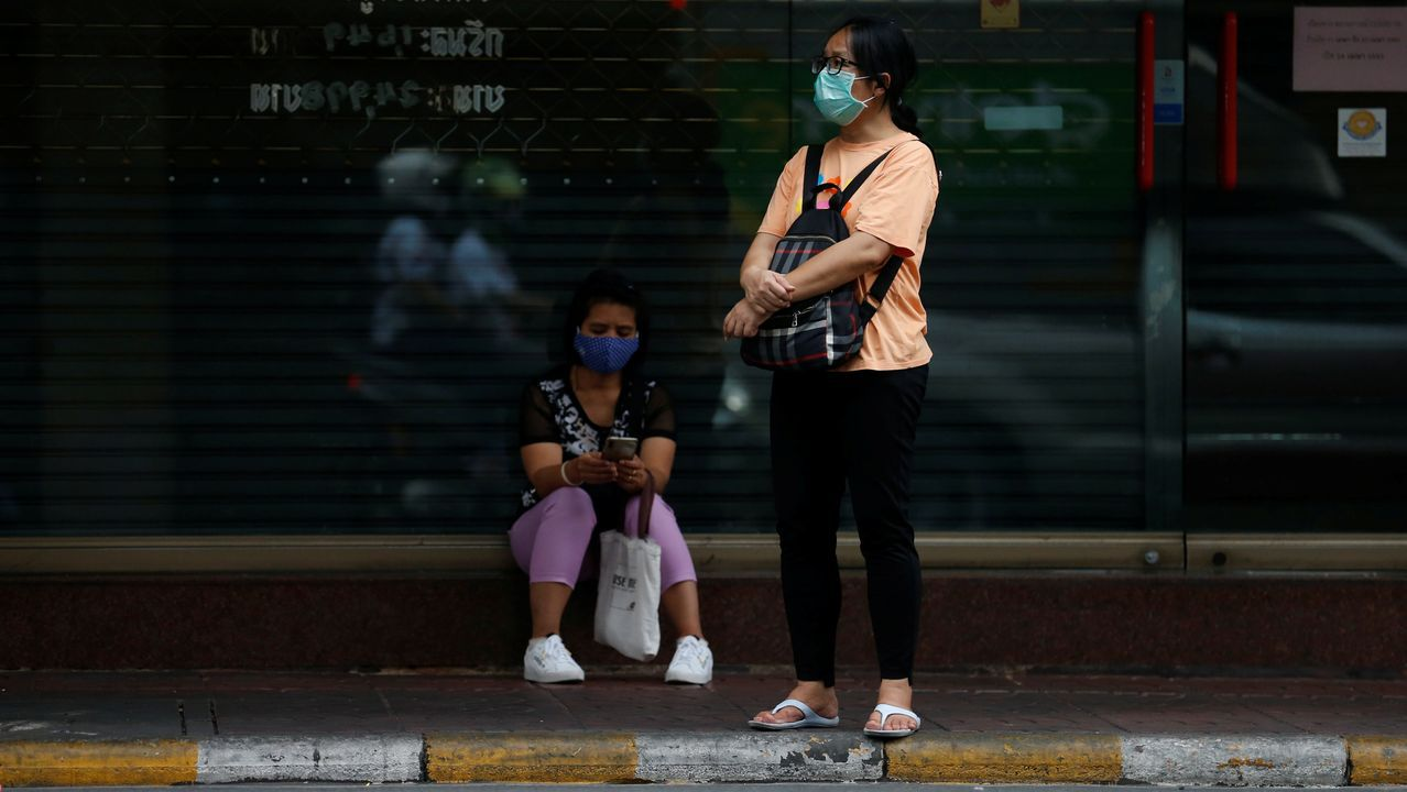 Mujeres con mascarillas protectoras esperan un autobús en Bangkok