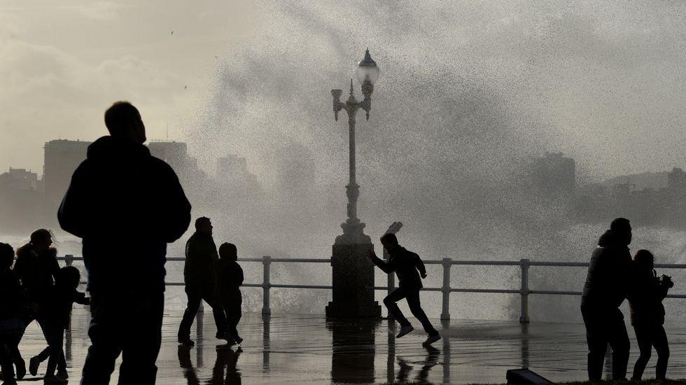 A Coruña, entre la niebla.El temporal marítimo congregó a multitud de vecinos en el Muro de San Lorenzo, en Gijón