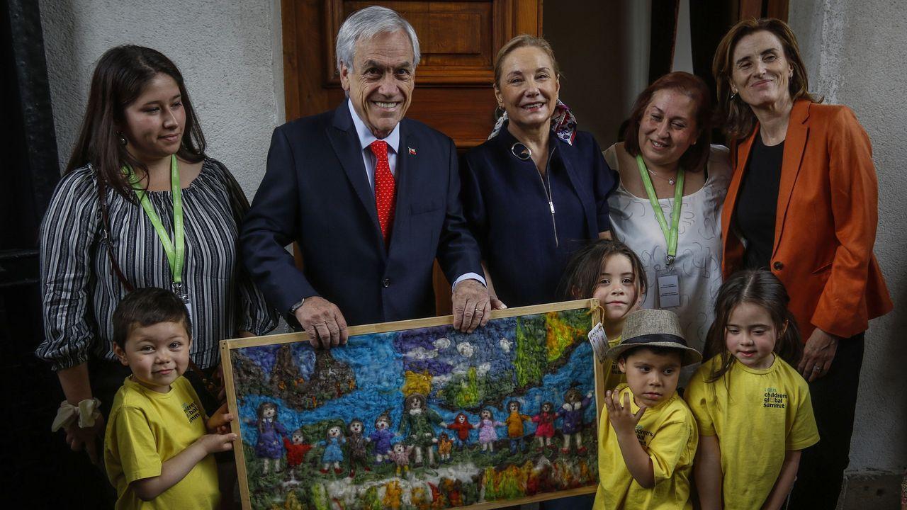 Piñera posa con un cuadro que le regalaron unos escolares el dia de su cumpleaños
