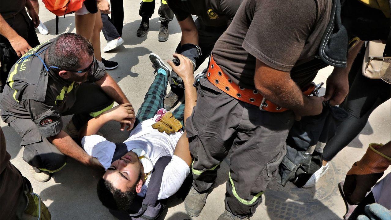 Los enfrentamientos entre la policía y los manifestantes en Beirut.Un manifestante herido es atendido por miembros de los servicios de rescate