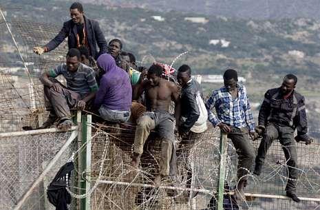 Inmigrantes encaramados en la valla de Melilla en la zona de Aguadú, el pasado día 3.