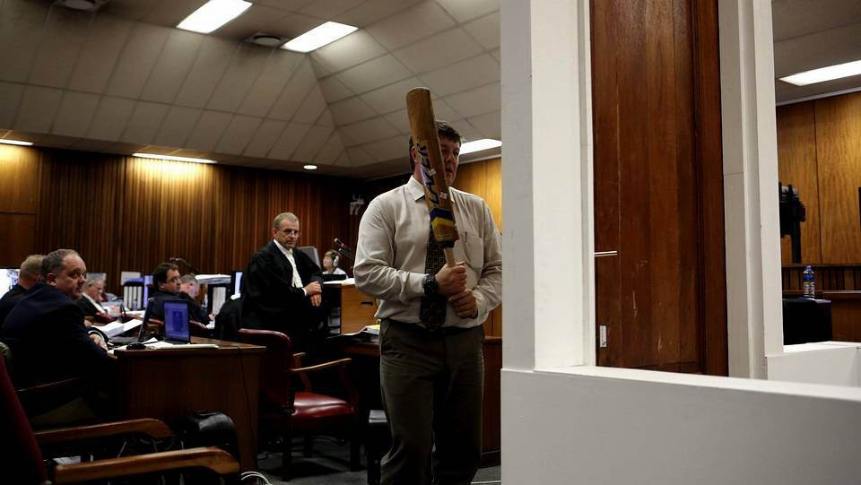 Un policía participa en la reconstrucción de la rotura de la puerta con el bate de crícket durante la octava jornada del juicio contra el atleta paralímpico Óscar Pistorius