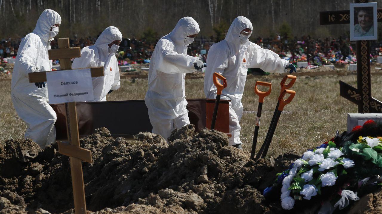 Trabajadores de un cementerio de San Petersburgo entierran a un fallecido por coronavirus en un área especial reservada en el camposanto