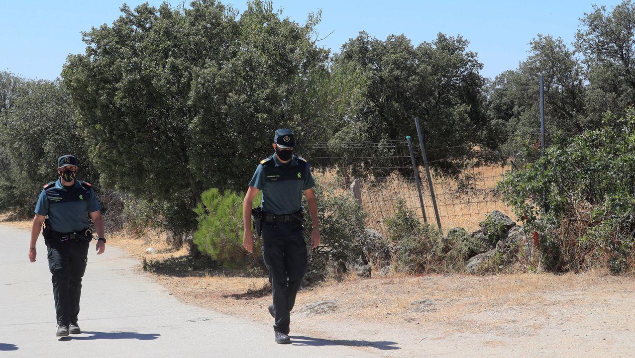 Dos guardias civiles patrullan por el lugar donde se encontraron los restos de la mujer de 70 años presuntamente asesinada por su hija y su yerno
