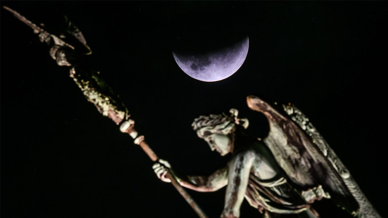 El eclipse, sobre una de las figuras de la Puerta de Brandenburgo, en Berlín