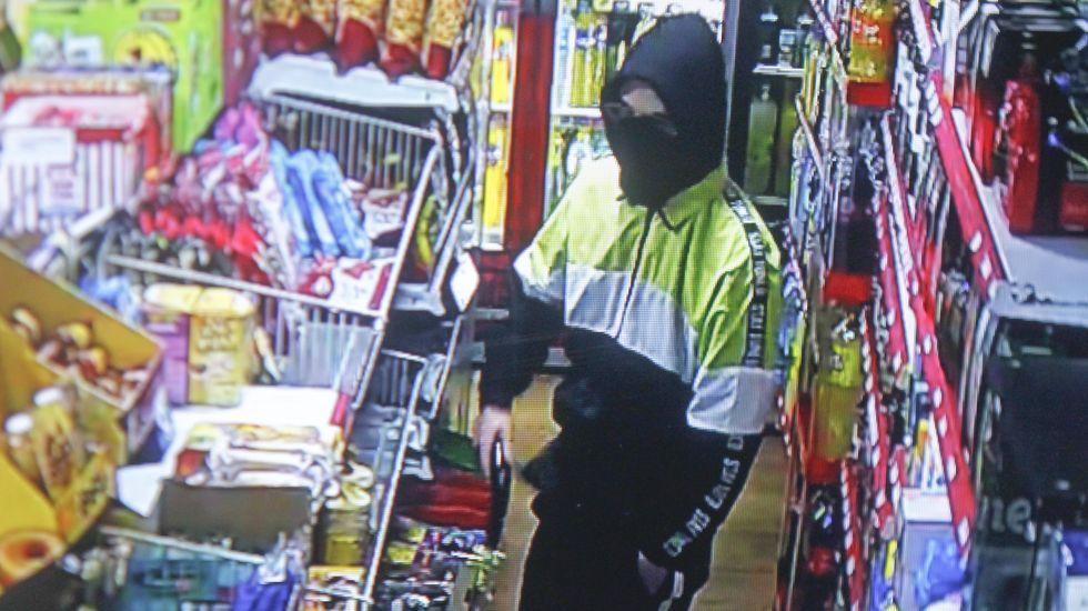 Captura de una de las imágenes grabadas por la cámara de videovigilancia donde se aprecia el arma que el presunto atracador sacó del pantalón