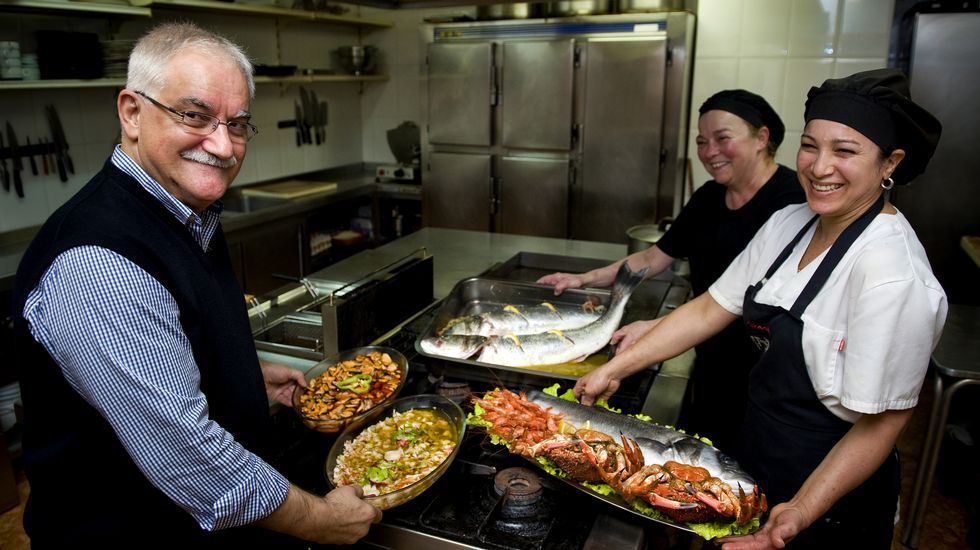 RICARDO. El dueño del céntrico restaurante coruñés, Ricardo Ventura, junto a Domi, cocinera, y Conchi, ayudante de cocina, con algunos de los platos más demandados