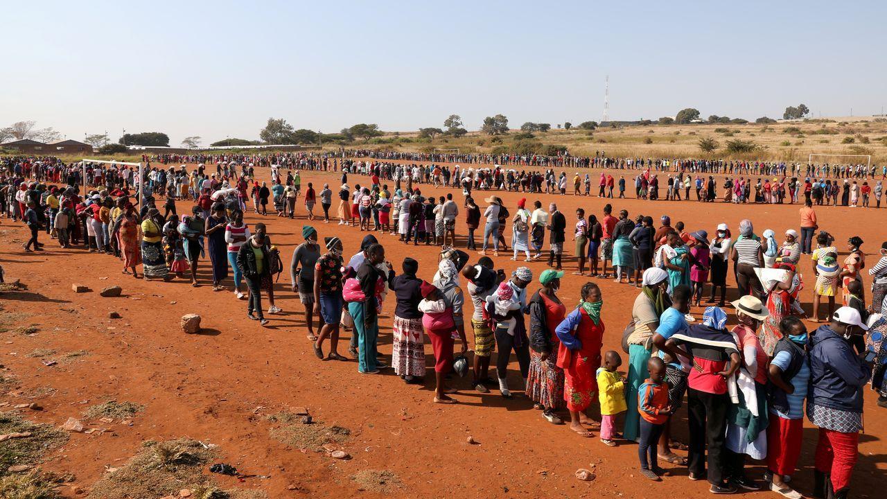 La gente hace fila para recibir ayuda alimentaria en medio de la propagación de la enfermedad por coronavirus, en el asentamiento informal de Itireleng, cerca del suburbio de Laudium en Pretoria, Sudáfrica