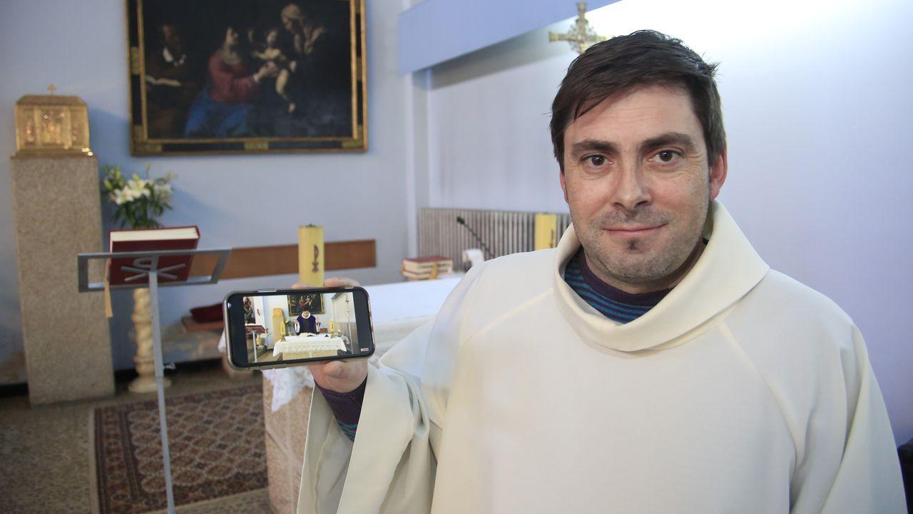 El párroco José Luis Vázquez con el móvil que utiliza para grabar las misas que difunde cada día en YouTube