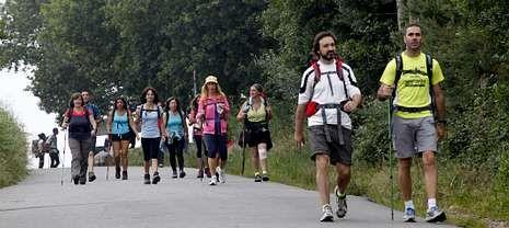 Cuatro peregrinos cruzan la Praza 8 de Marzo de Cee en su caminata hacia Fisterra.