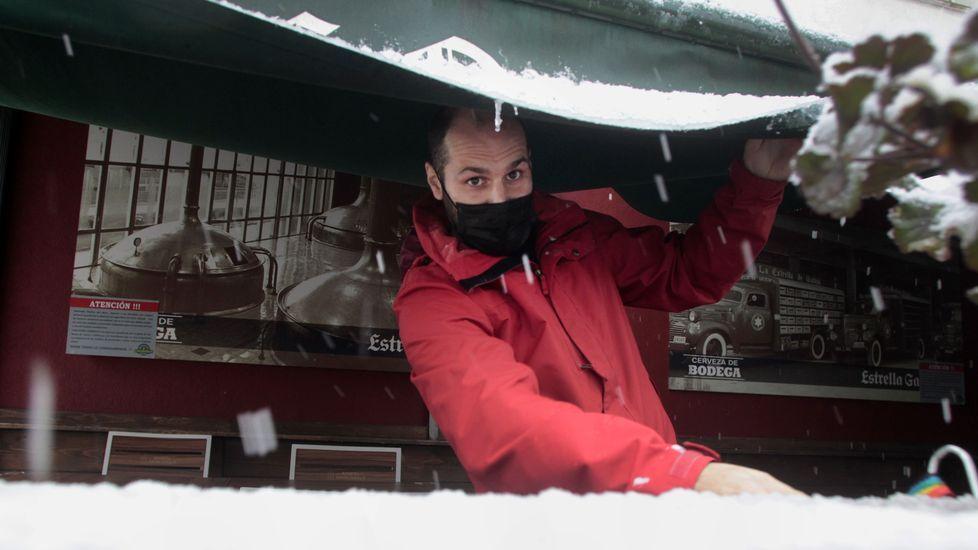 El propietario de un bar de Bóveda cierra el toldo para evitar que el peso de la nieve lo rompa