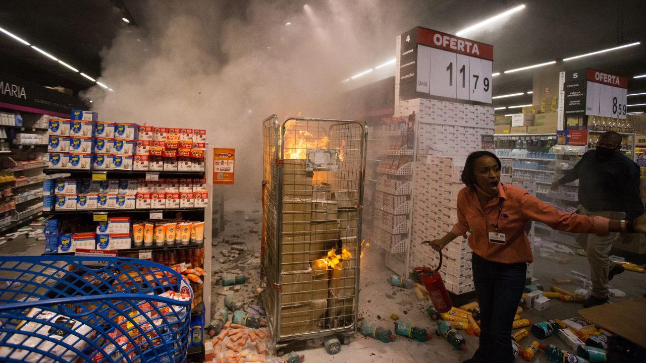 Una empleada intenta apagar el fuego provocado por los manifestantes
