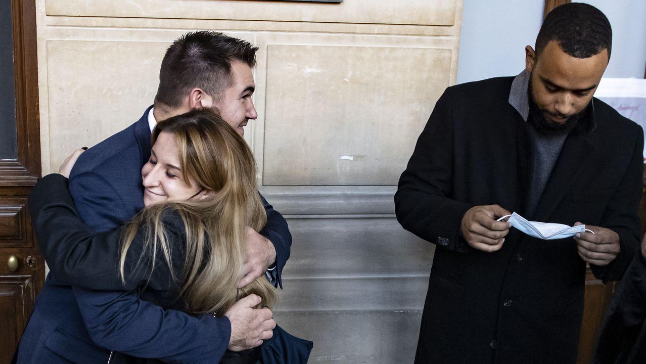 Una empleada del tren Thalys abraza al estadounidense Alek Skarlatos, que espera con Anthony Sadler su entrada en la sala donde tiene lugar el  juicio por ataque terrorista
