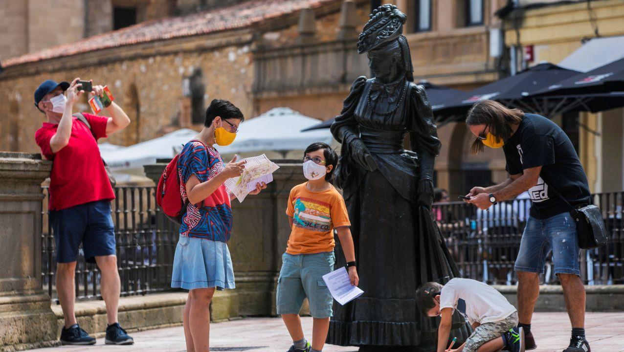 Varios turistas con mascarilla observan la escultura de la Regenta en la plaza de la catedral de Oviedo