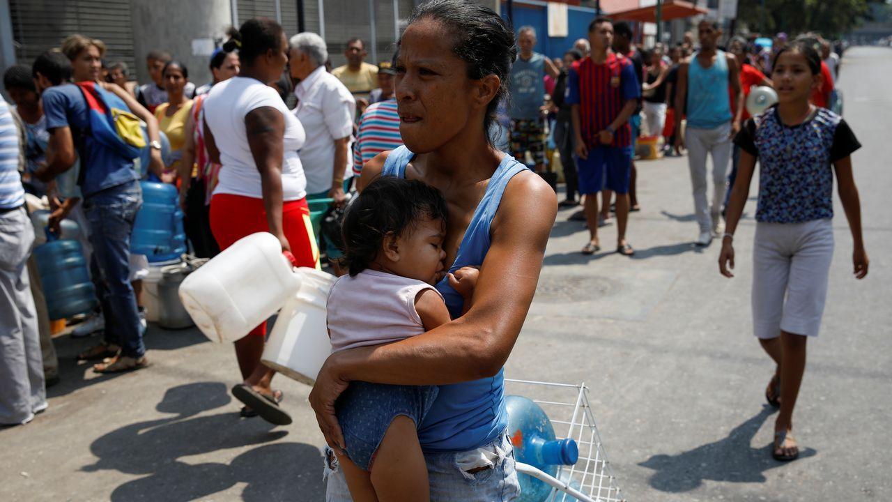 Un grupo de pasajeros consulta los vuelos en el Aeropuerto de Asturias.Una mujer cargando con su bebé se dispone a hacer cola para aprovisionarse de agua en Caracas