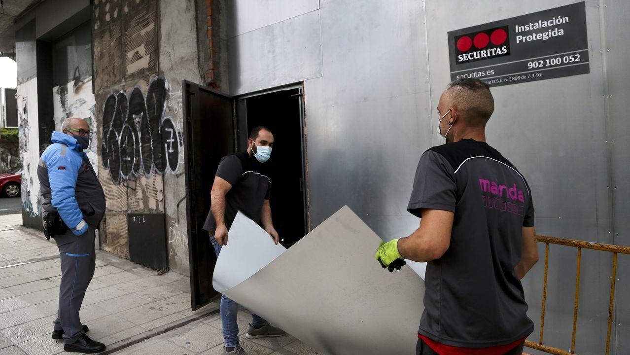 Dos operarios y un vigilante sellando un edificio okupa de Vigo