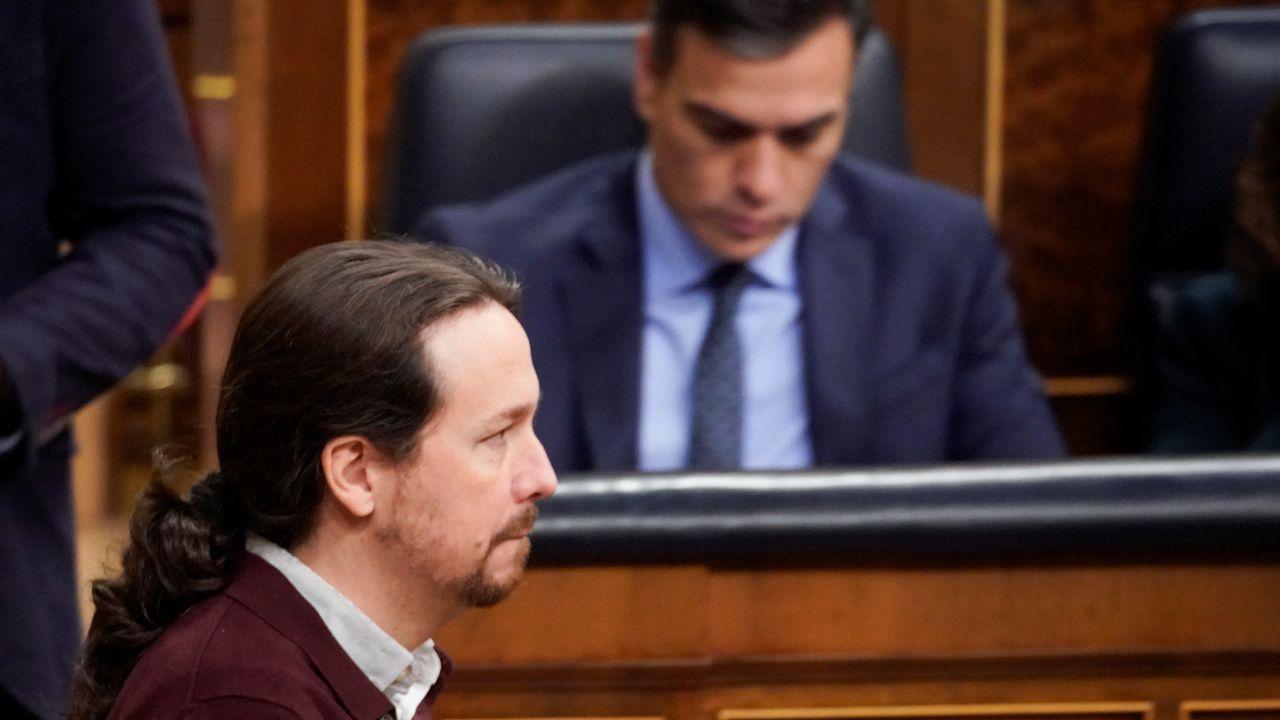 Teléfono móvil.El líder de Unidas Podemos, Pablo Iglesias, pasa por delante de Pedro Sánchez