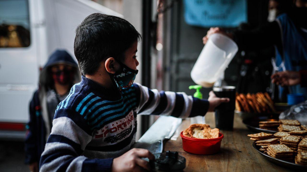 Un niño espera que le sirvan un vaso de leche el 29 de julio de 2020, en un comedor comunitario de Buenos Aires, Argentina