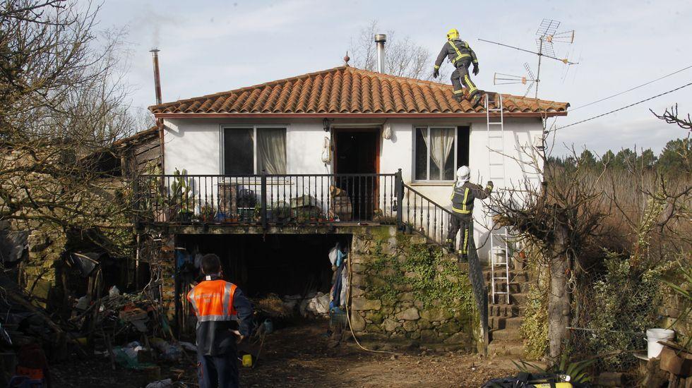 Un bombero sube al tejado de la casa del incendio de Liñarán para comprobar el estado de la salida de humo de la chimenea