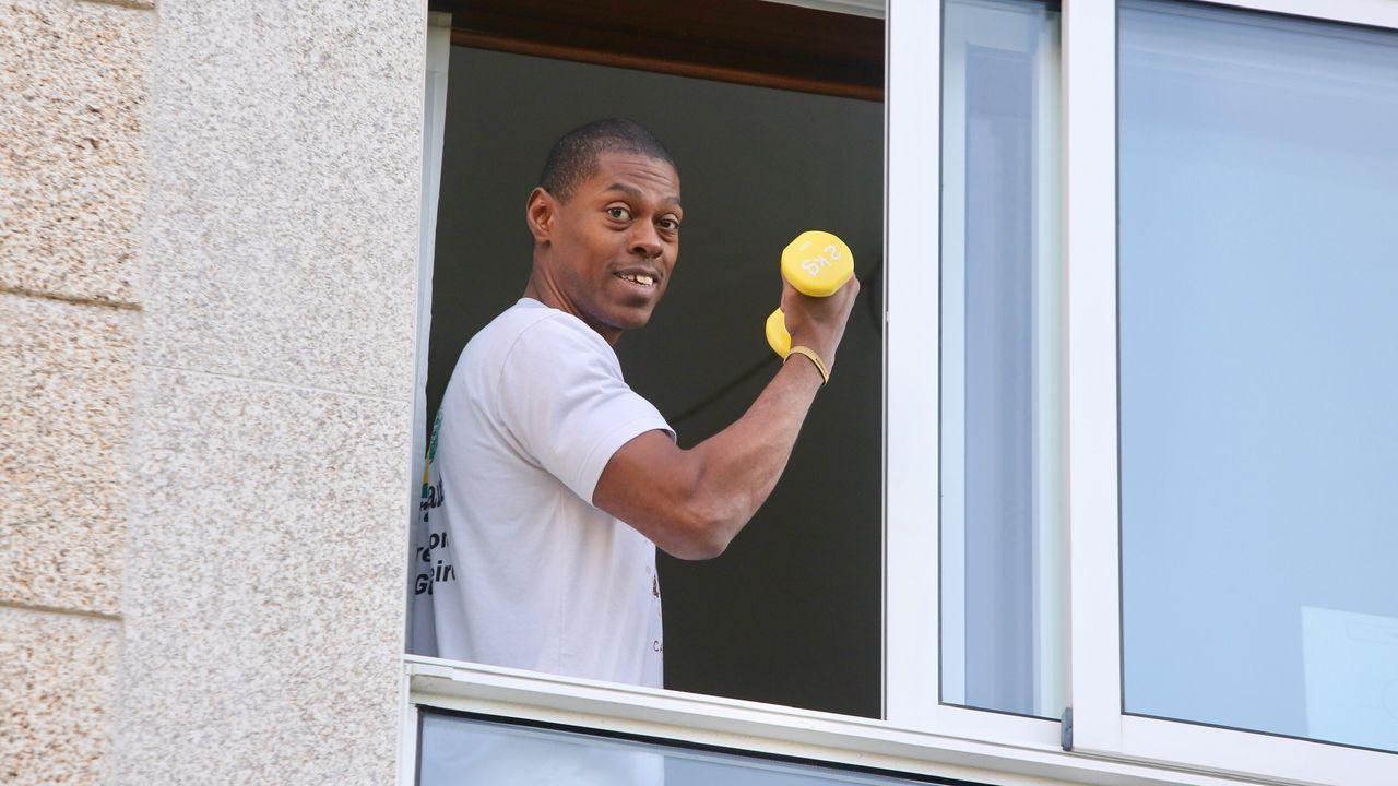 Una persona confinada en casa por el coronavirus aprovecha su ventana para hacer ejercicio físico con unas pesas