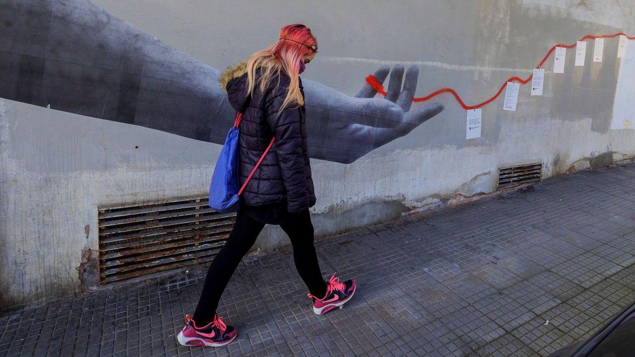 huerta.Una mujer pasa por delante de un mural en Siero