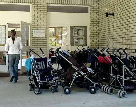 Una mujer pasa ante los carritos aparcados a las puertas de una guardería pública de la ciudad.