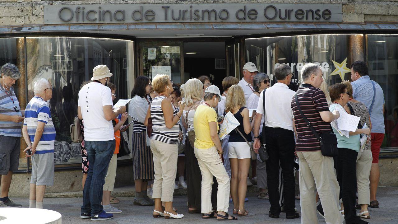 Un grupo de visitantes hace cola a las puertas de una oficina de información turística en la ciudad de Ourense