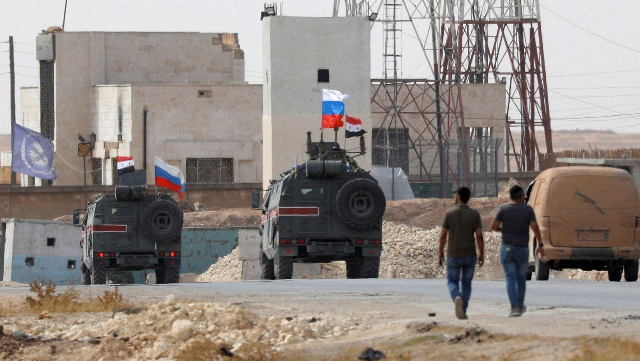 Vehículos militares con banderas rusas y sirias pasan por el antiguo cuartel de la tropas estadounidenses en Manbij