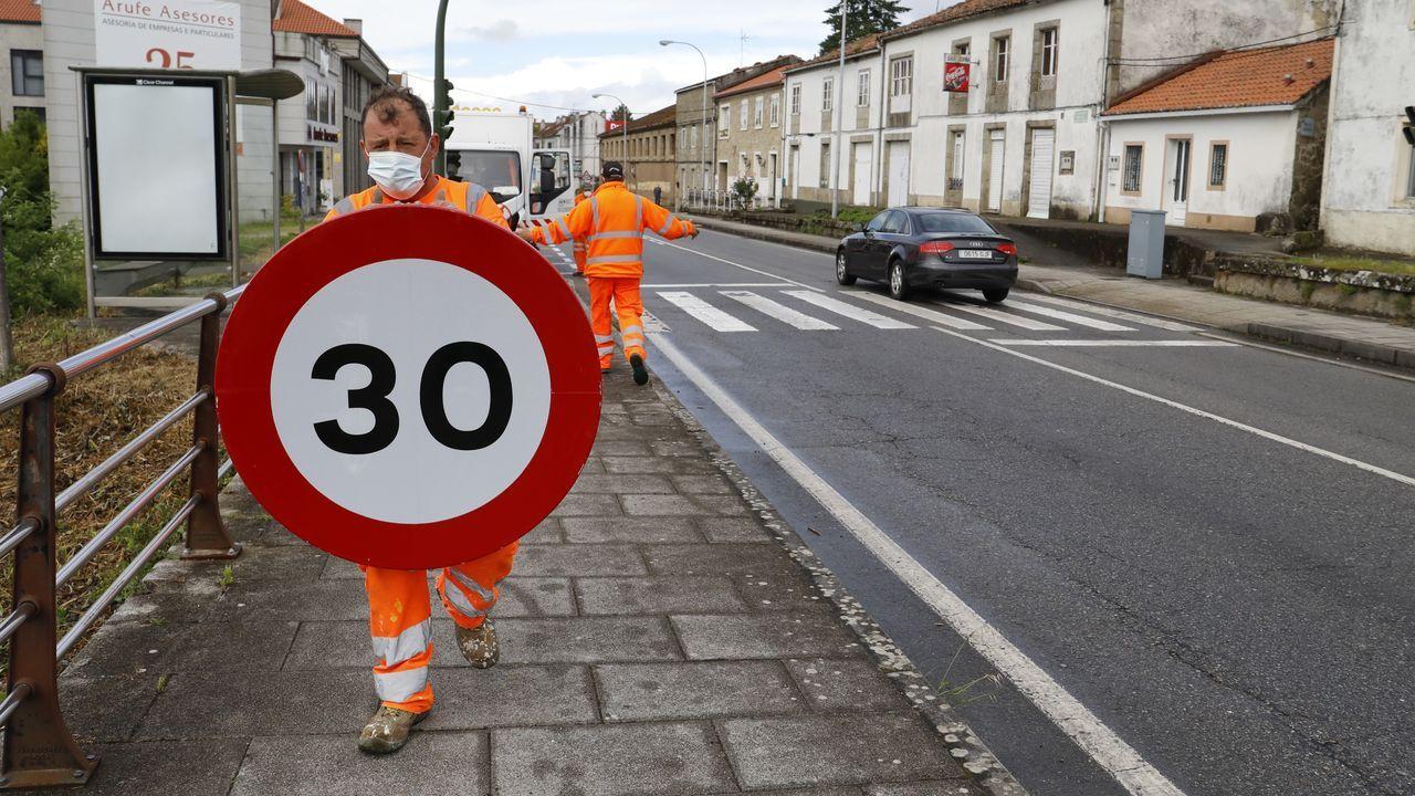 Operarios cambiando la señalización en Santiago este lunes