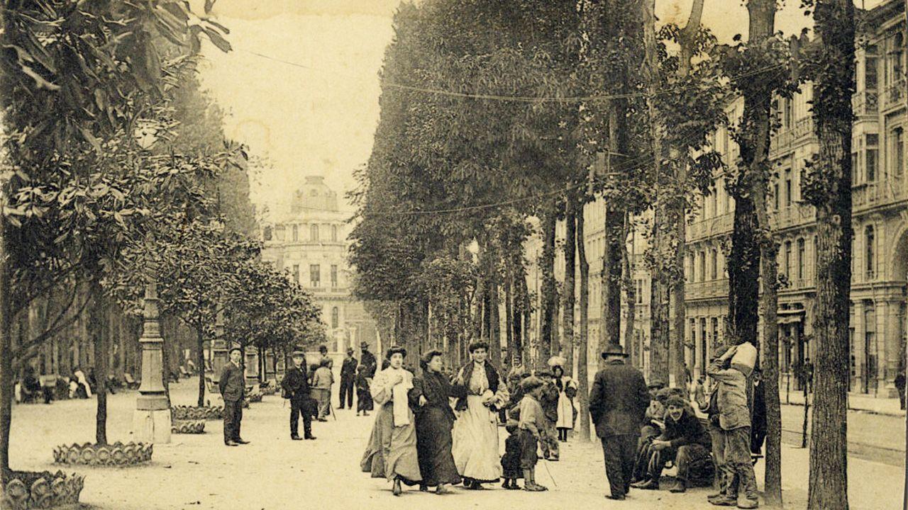 Una de las primeras imágenes del paseo de los Álamos, hacia 1910, donde se aprecian los grandes ejemplares y se atisba a la derecha el antiguo pasaje de Uría. Ese arco ha desparecido. Al fondo se ve también el palacete de la esquina de Uría con Torenta, igualmente derribado