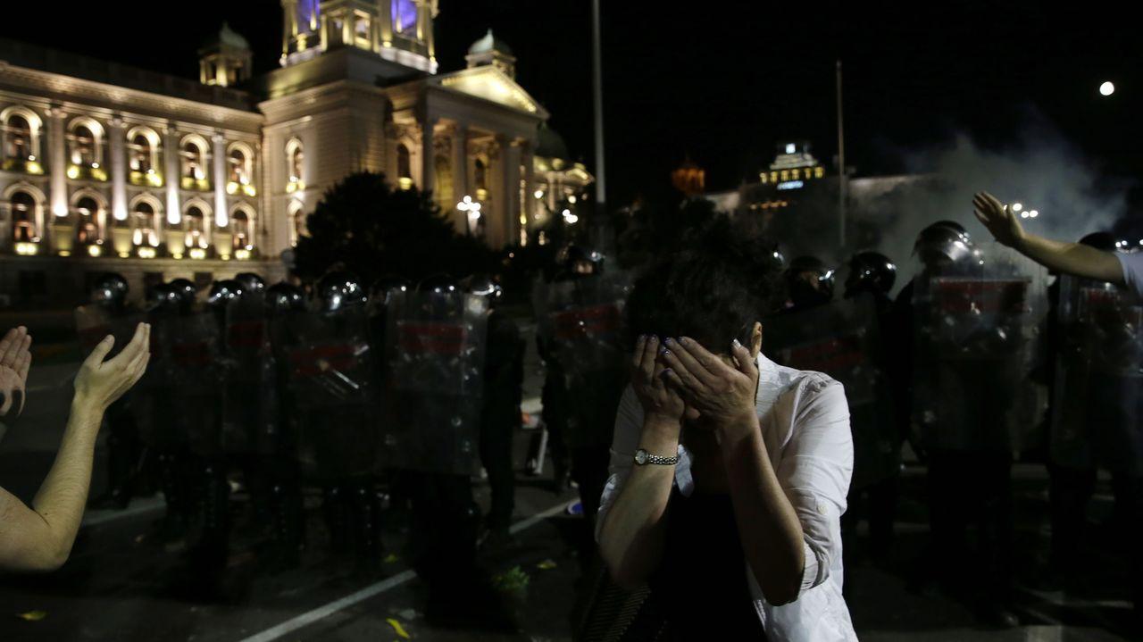 Así será el protocolo para votar en las autonómicas.Una mujer cubre sus ojos en medio de las protestas al frente del parlamento serbio
